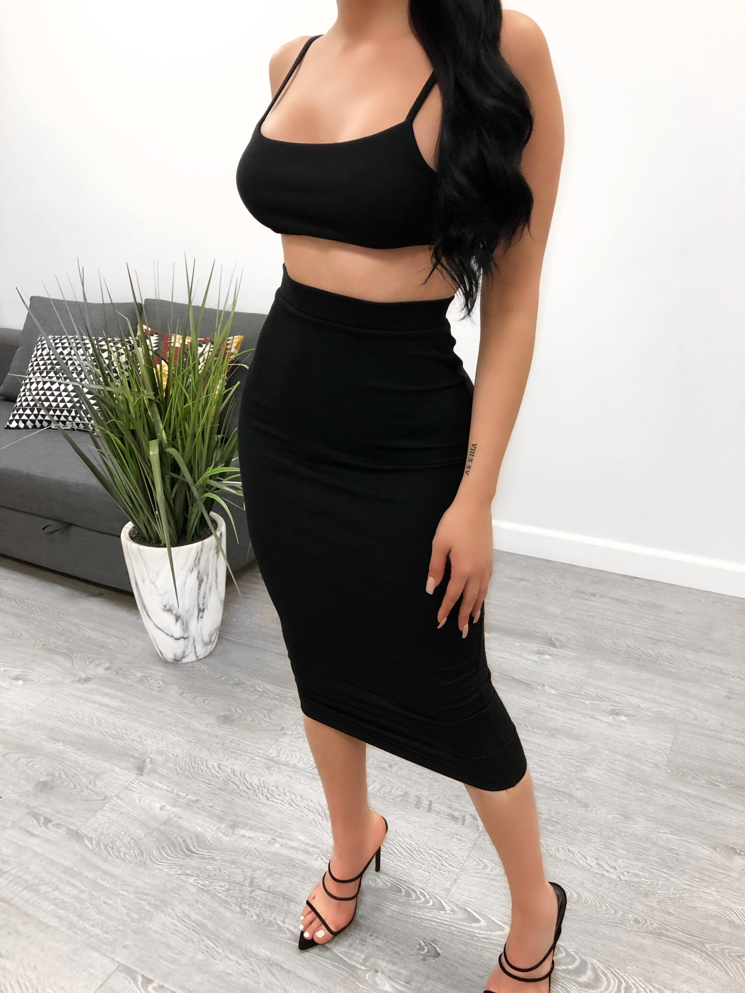 black two piece set. backless top. non adjustable strap on back for support. high waisted skirt. skirt is below the knee length.