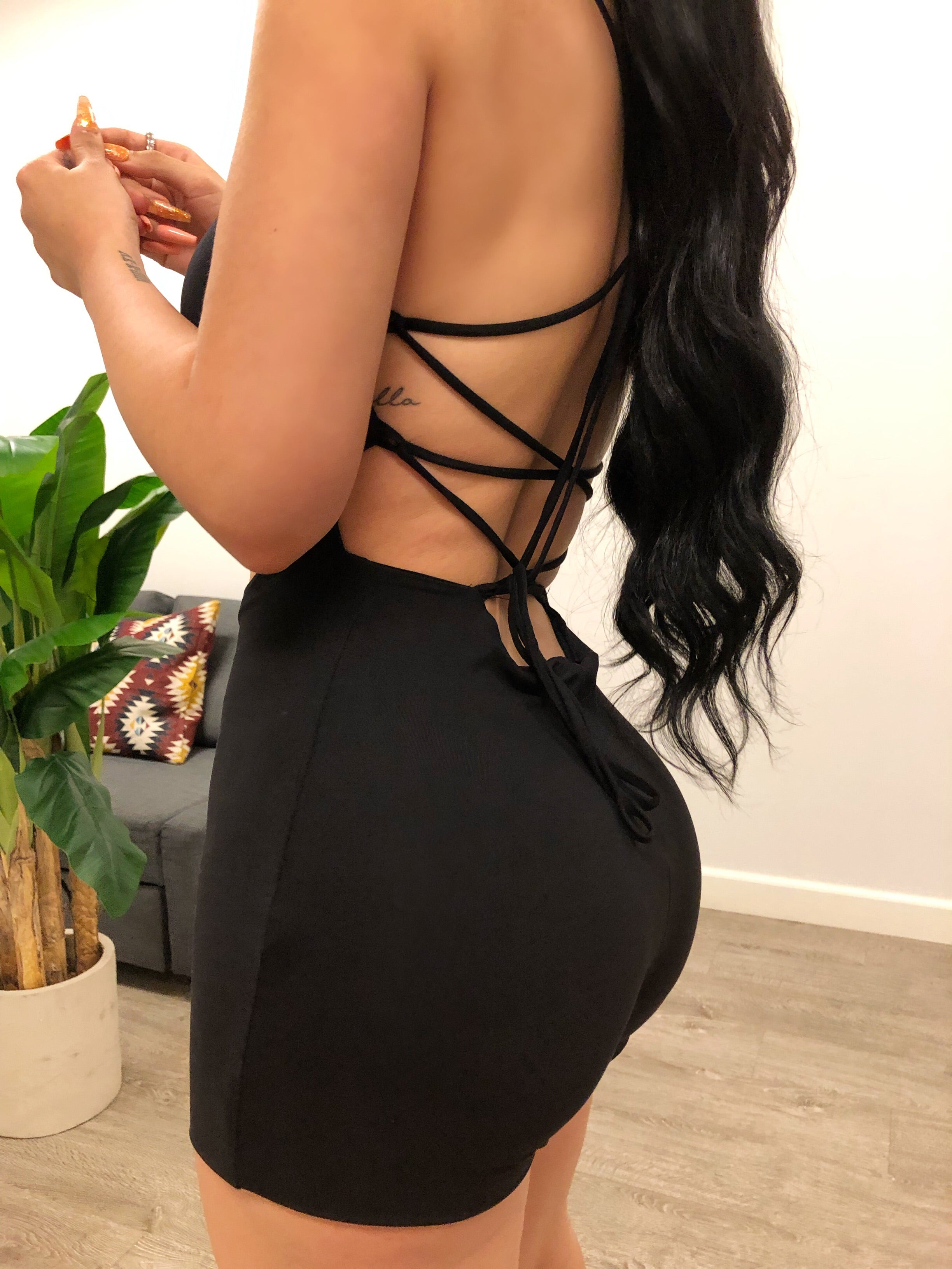 black spaghetti strap skin tight romper, U shape neckline showing mid cleavage, oval shaped opening on stomach area, bottom ends mid thigh, back has strings that criss cross and tie up at the bottom