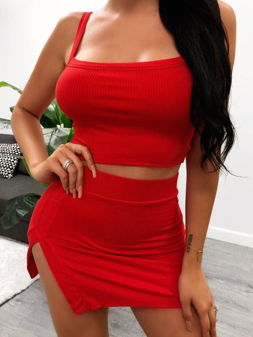 red two piece set. cropped tank top.  non adjustable straps. shows no cleavage. short high waisted skirt. skirt has a slit on outer right side. above mid thigh length.