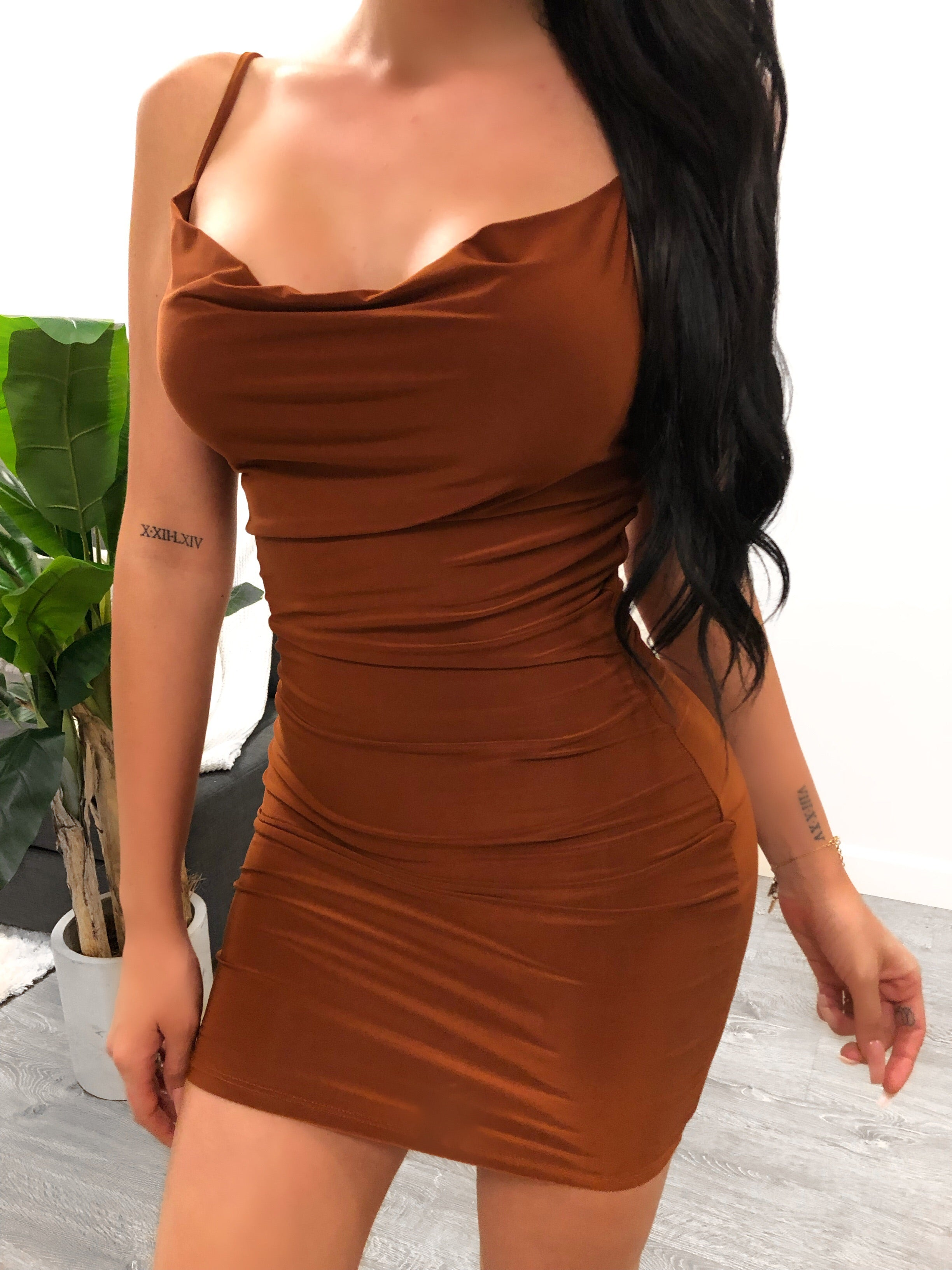 cognac color spaghetti strap skin tight dress, neck line is loose fit, showing mid cleavage, dress ends mid thigh