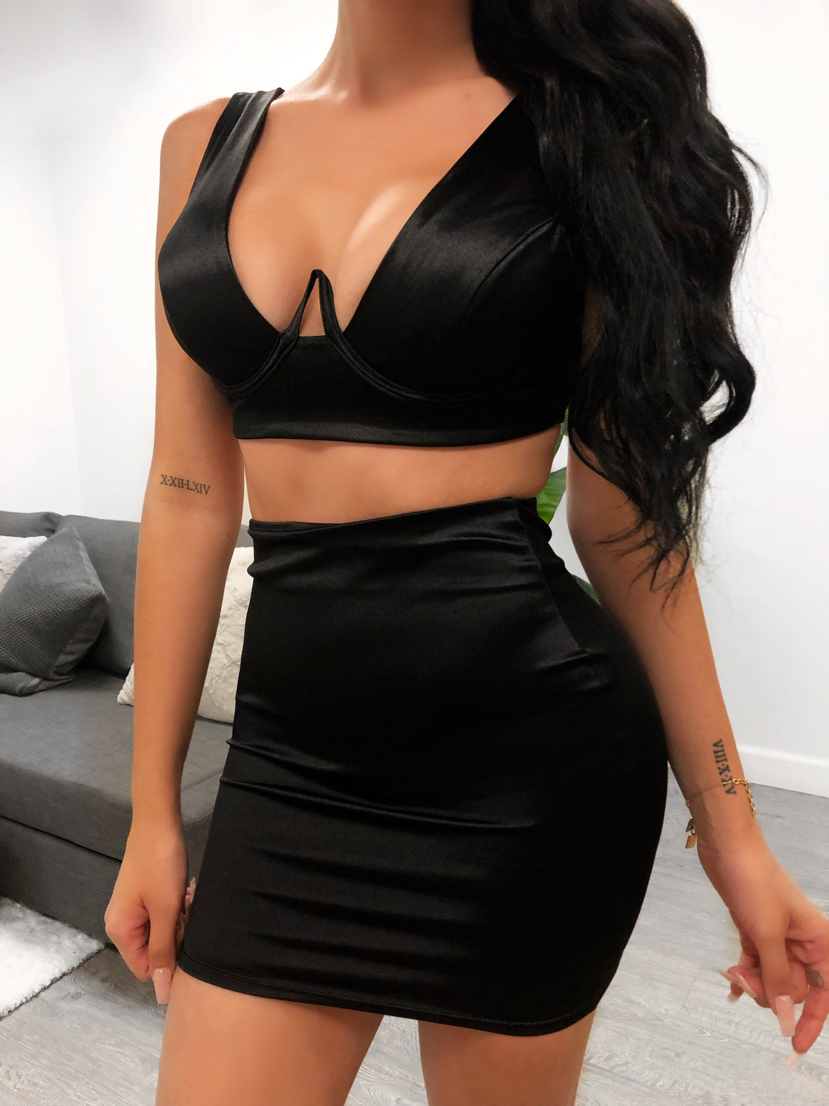 black satin 2 piece, top has u shape neckline showing half cleavage crop top, sleeveless, strap are 4 fingers wide, bottoms is a black high was it skirt that ends mid thigh
