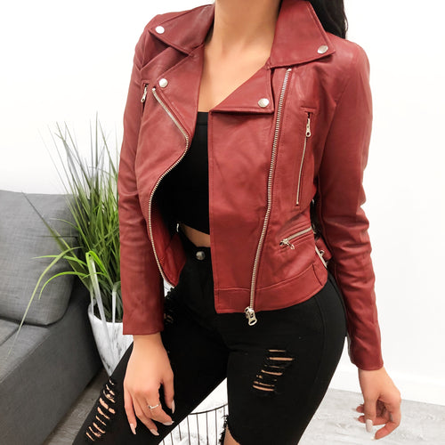 Burgundy leather biker jacket with silver buttons and zippers jacket length ends at belt line .