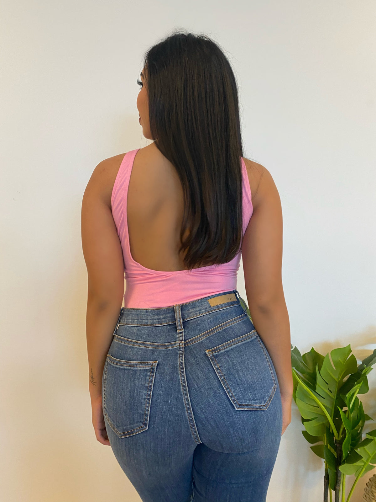 FITTED BODYSUIT, MID CLEAVAGE SHOWING, OPEN BACK, TWO-FINGER STRAPS, COLOR IS PINK.