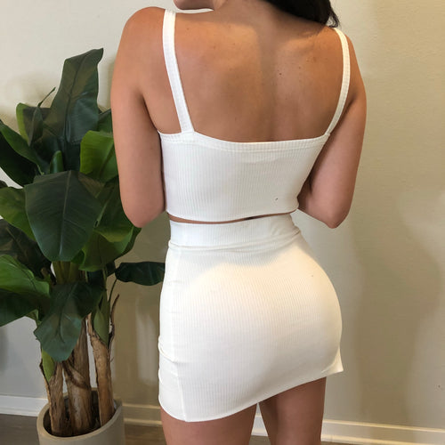 white two piece set. cropped tank top.  non adjustable straps. shows no cleavage. short high waisted skirt. skirt has a slit on outer right side. above mid thigh length.