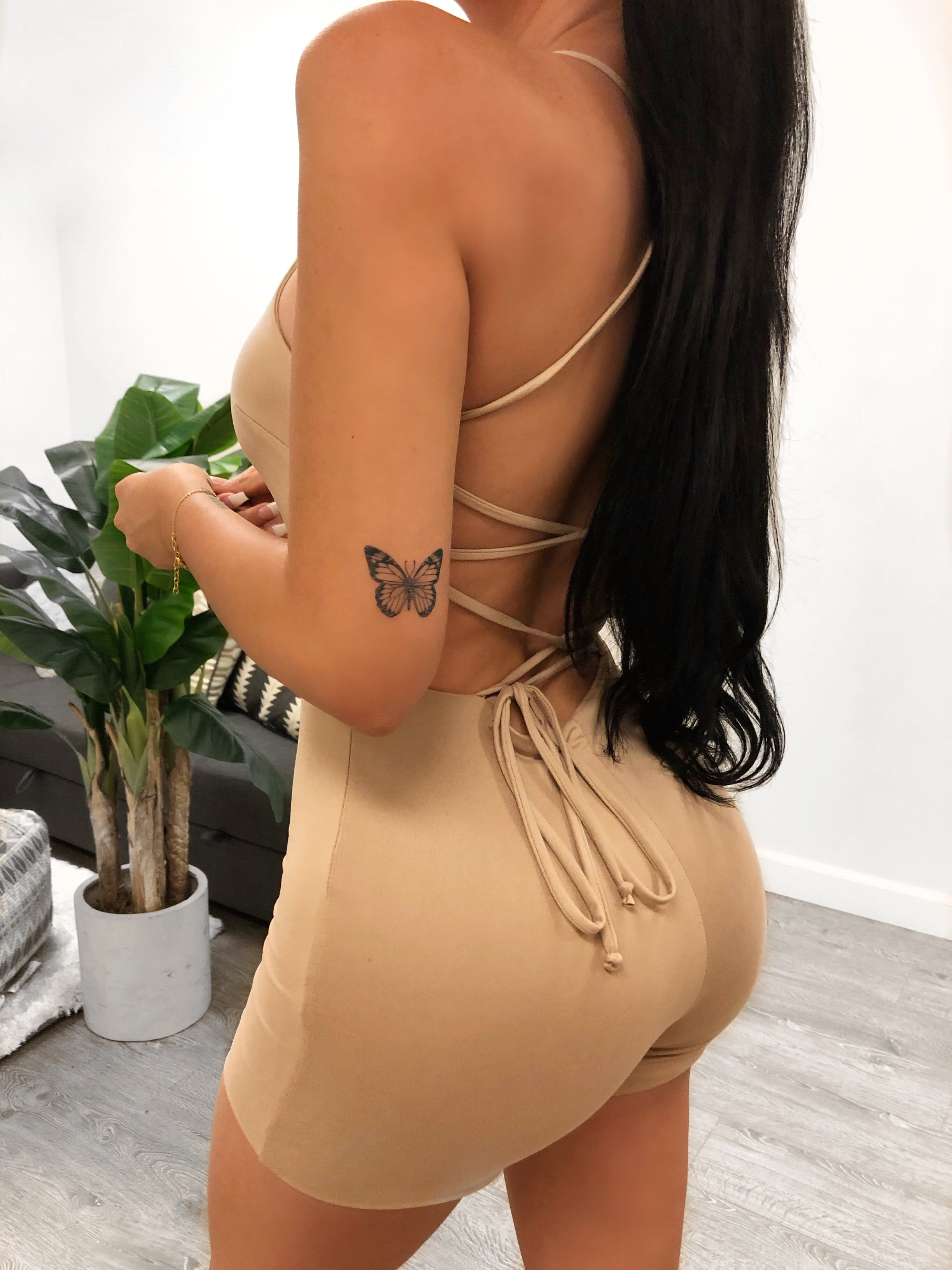 spaghetti strap skin tight romper, U shape neckline showing mid cleavage, oval shaped opening on stomach area, bottom ends mid thigh, back has strings that criss cross and tie up at the bottom