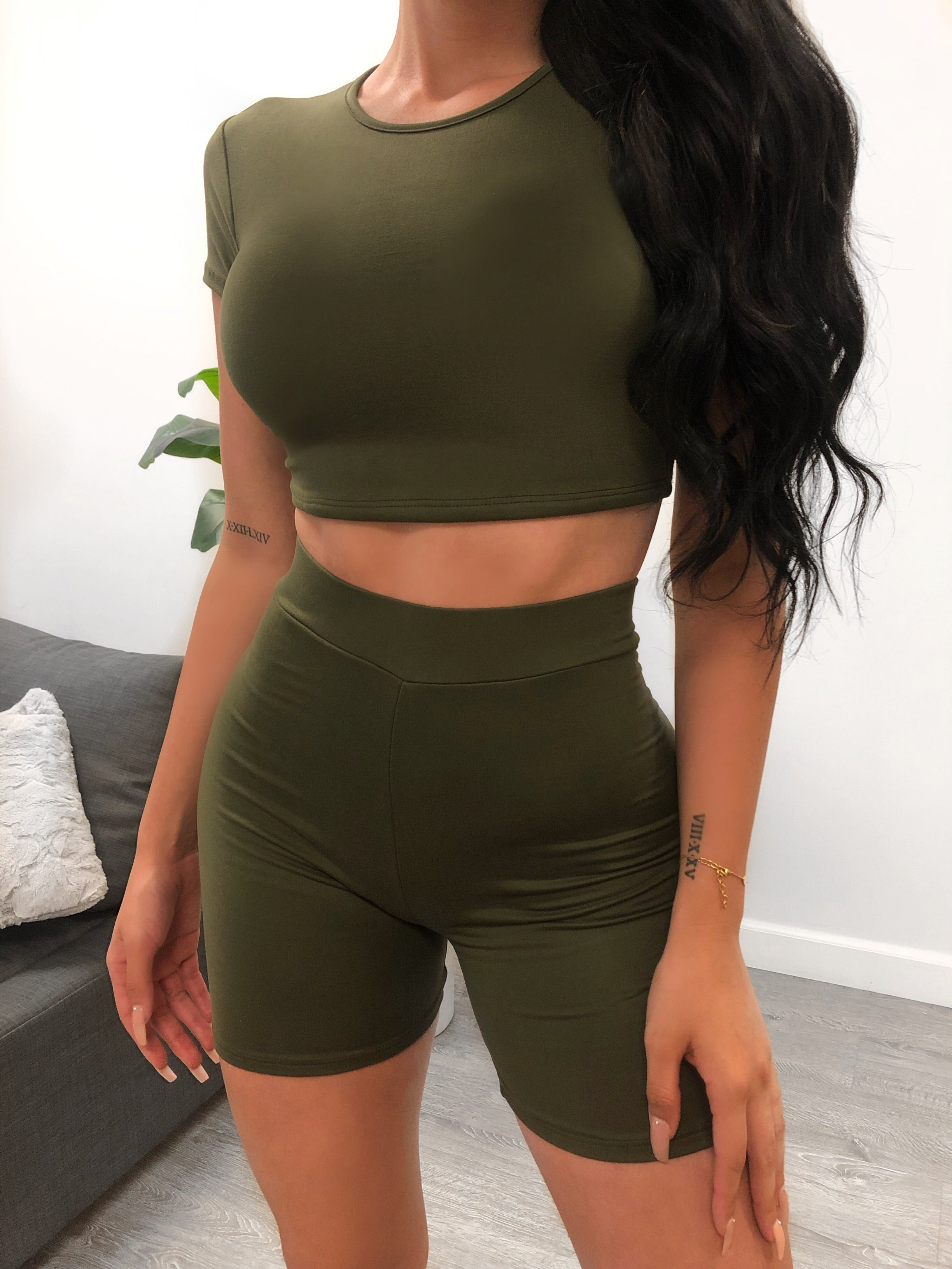 olive two piece, shirt is cropped crewneck and t-shirt sleeves. shorts are high waisted with elastic band at waist, shorts length are mid thigh.