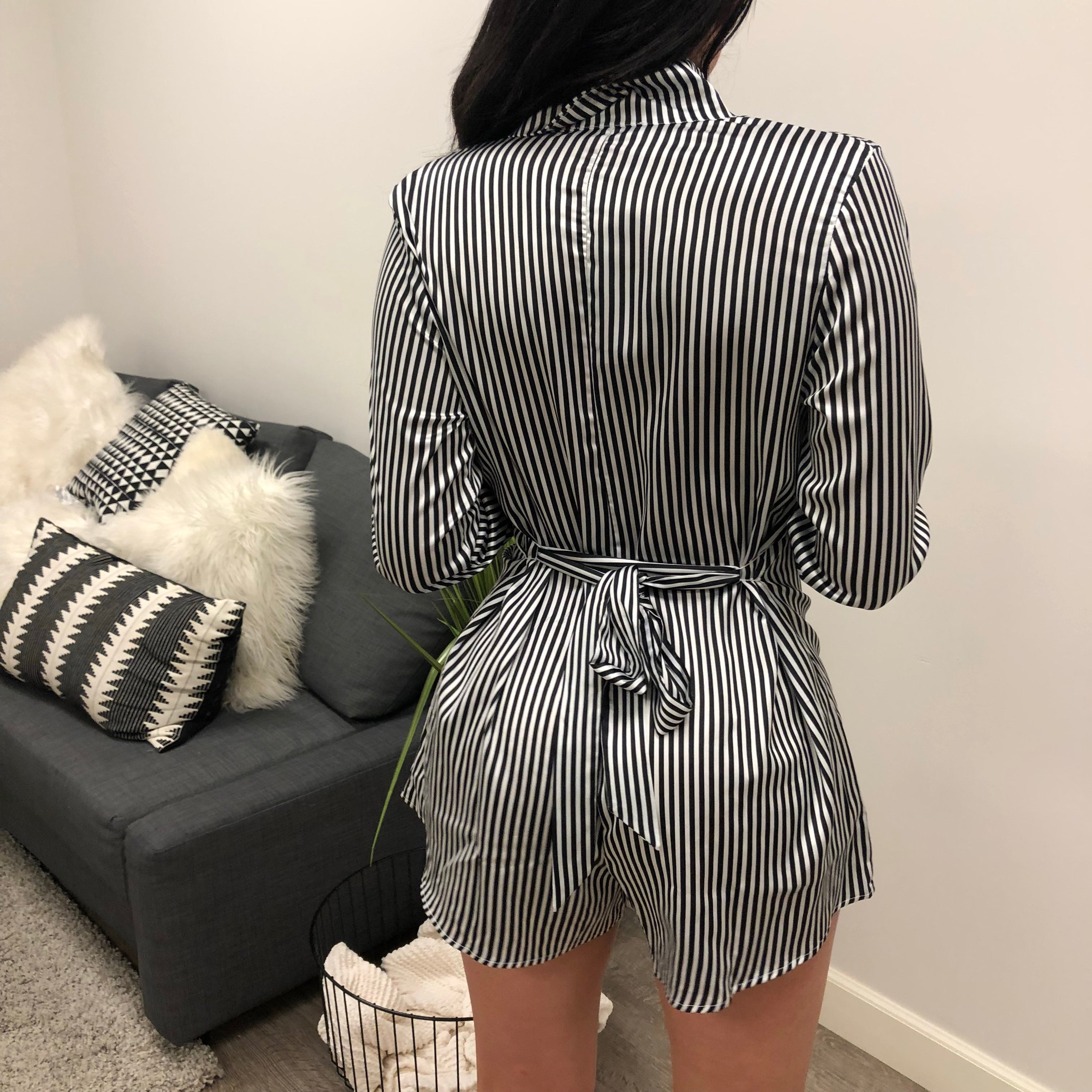 black and white vertical stripe romper. buttons in the chest area. collar long sleeve. collar neck. ties in the back.