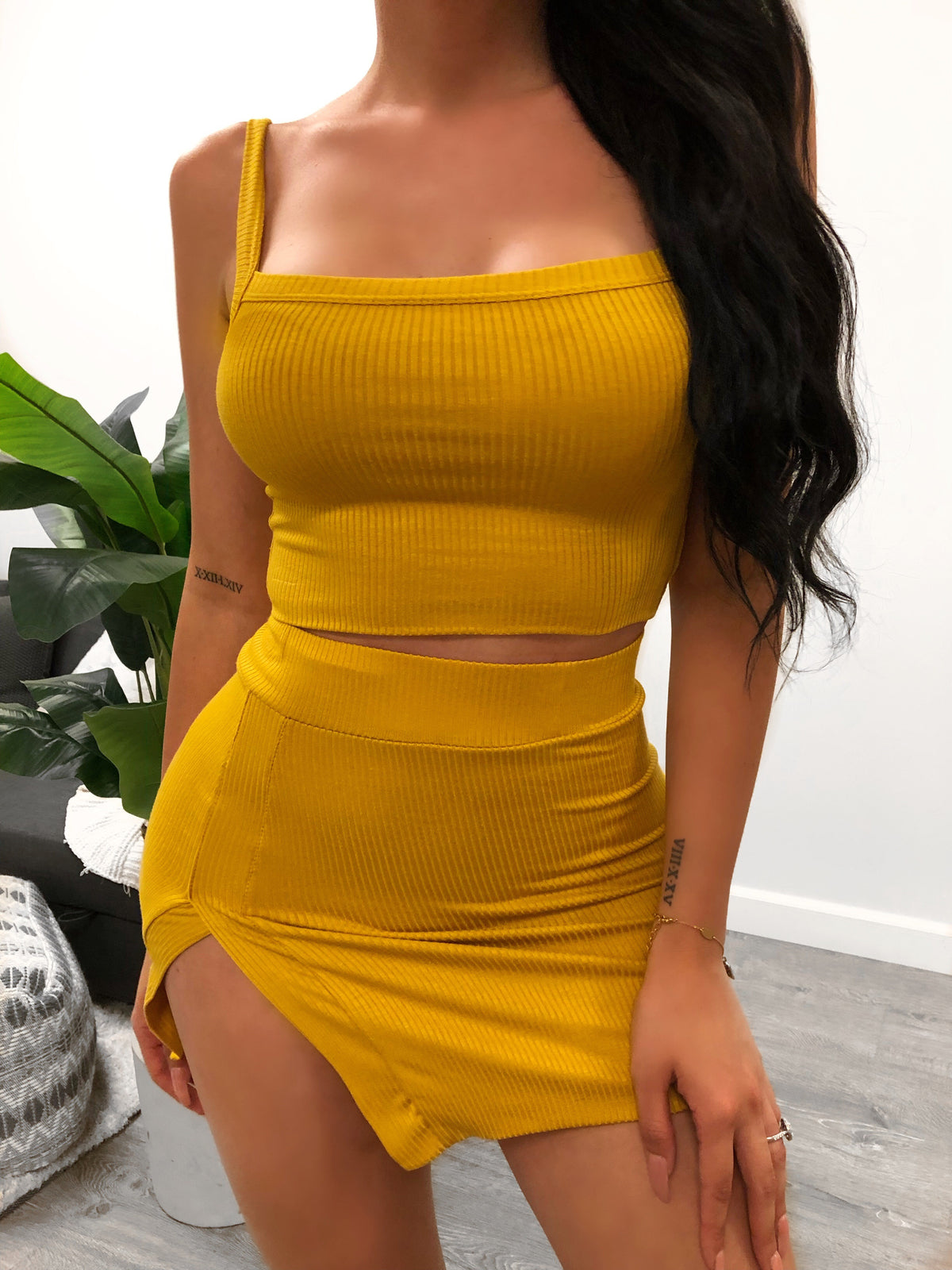 mustard yellow two piece set. cropped tank top.  non adjustable straps. shows no cleavage. short high waisted skirt. skirt has a slit on outer right side. above mid thigh length.