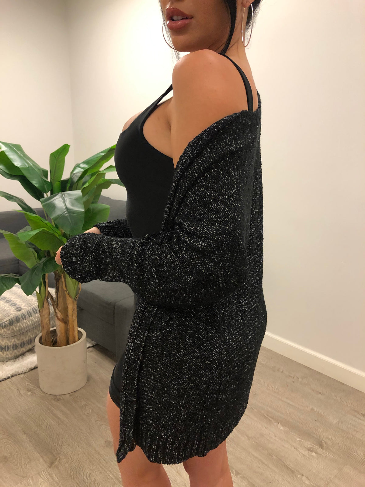 Black woven cardigan. Long sleeve and button-up. Loosely fitted. Mid-thigh length.