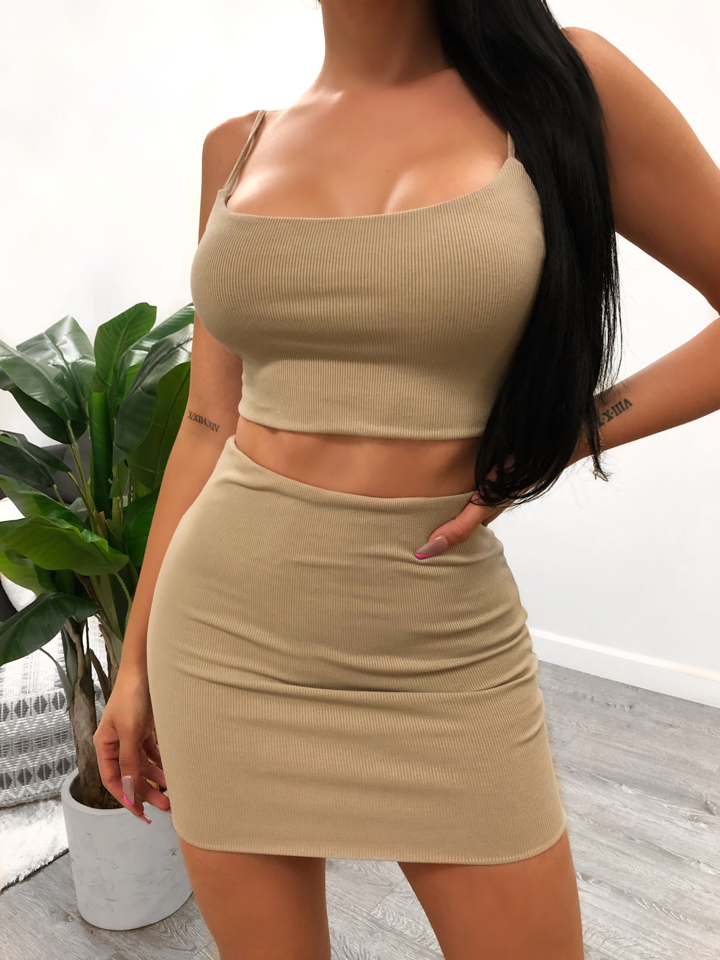 tan 2 piece set. crop top with adjustable spaghetti straps. skirt is above mid thigh length.