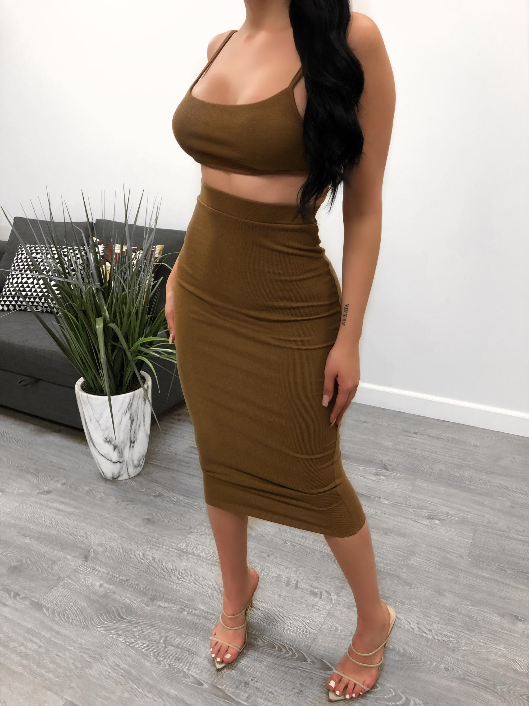 brown two piece set. backless top. non adjustable strap on back for support. high waisted skirt. skirt is below the knee length.