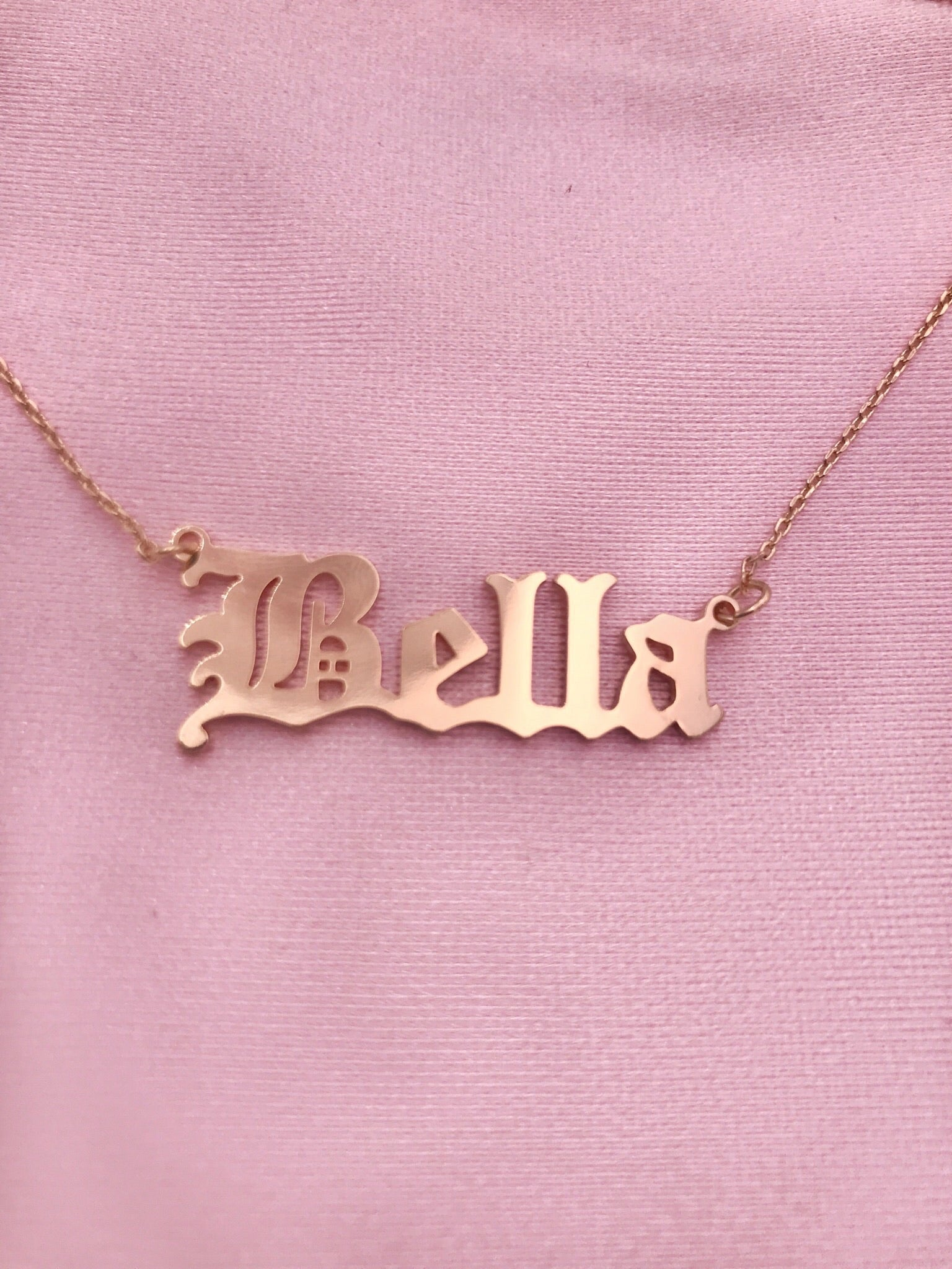 gold necklace spells out BELLA in old font. chain has clip at end