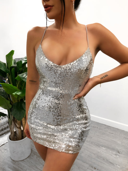 Silver sequined dress. Has non adjustable spaghetti straps. Dress is mid-thigh length and has a low u-cut top. Shows cleavage. Zips up the back.