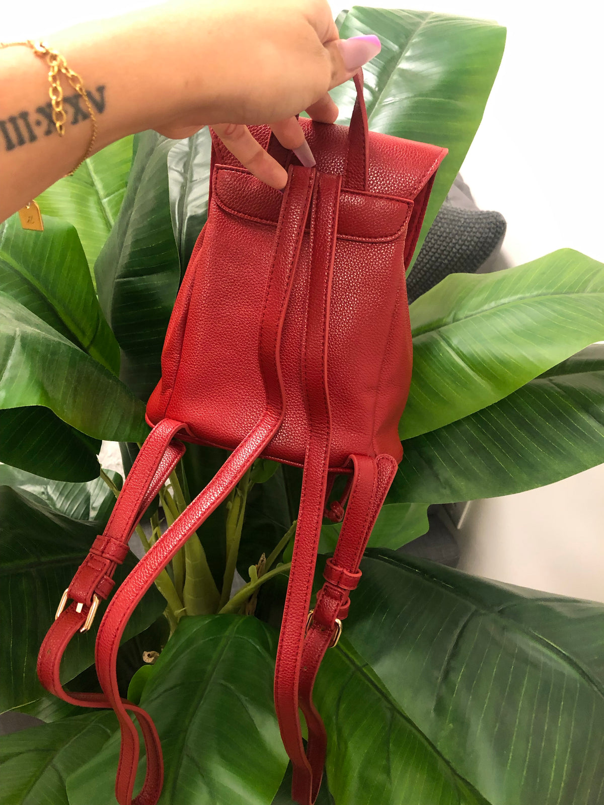 red pleather mini backpack with flap opening top.
