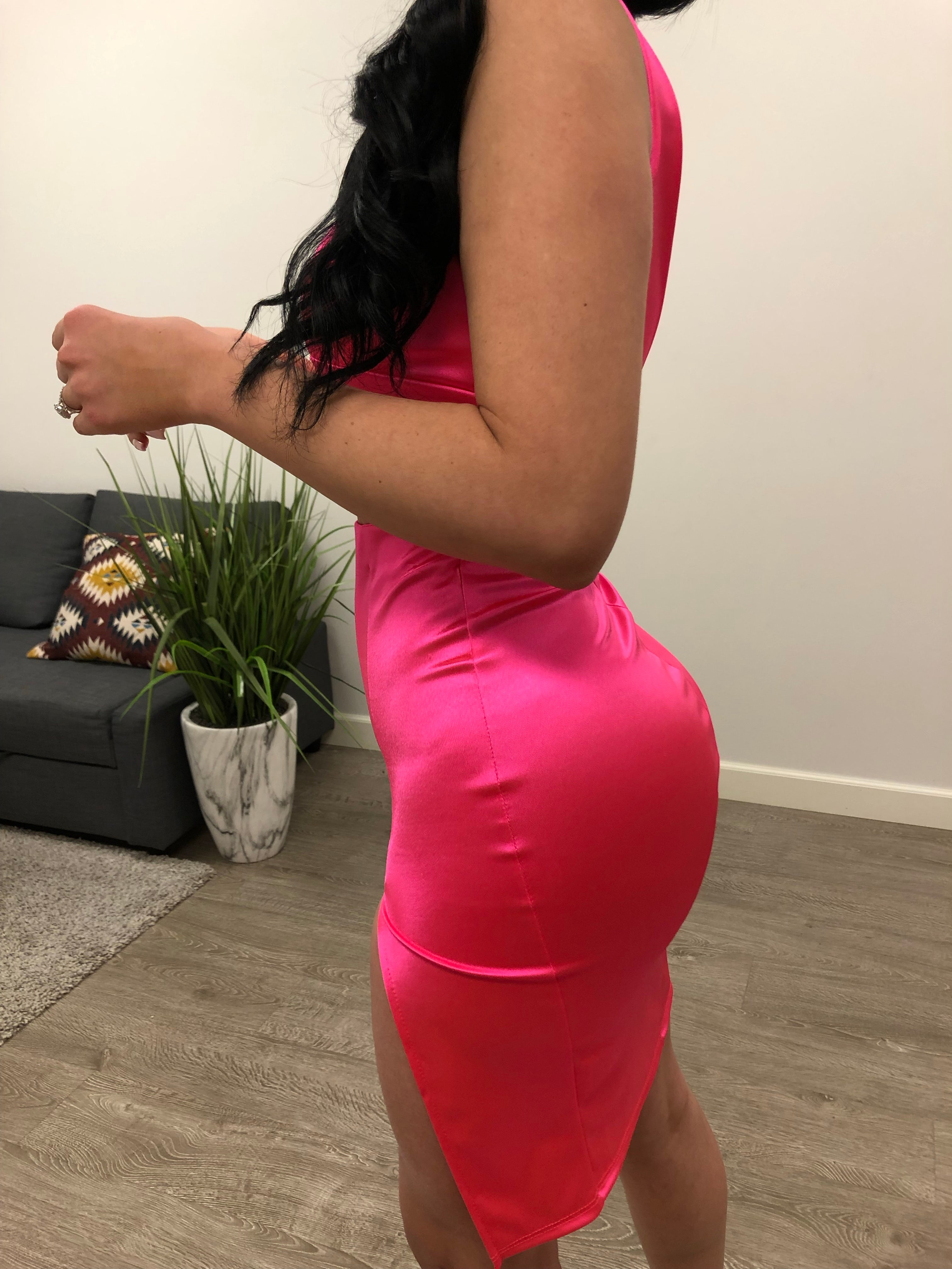 pink satin 2 piece, top has one spaghetti strap and one thick strap, low v cut neckline shows full cleavage length mid stomach , skirt length mid thigh , slit on left side of skirt