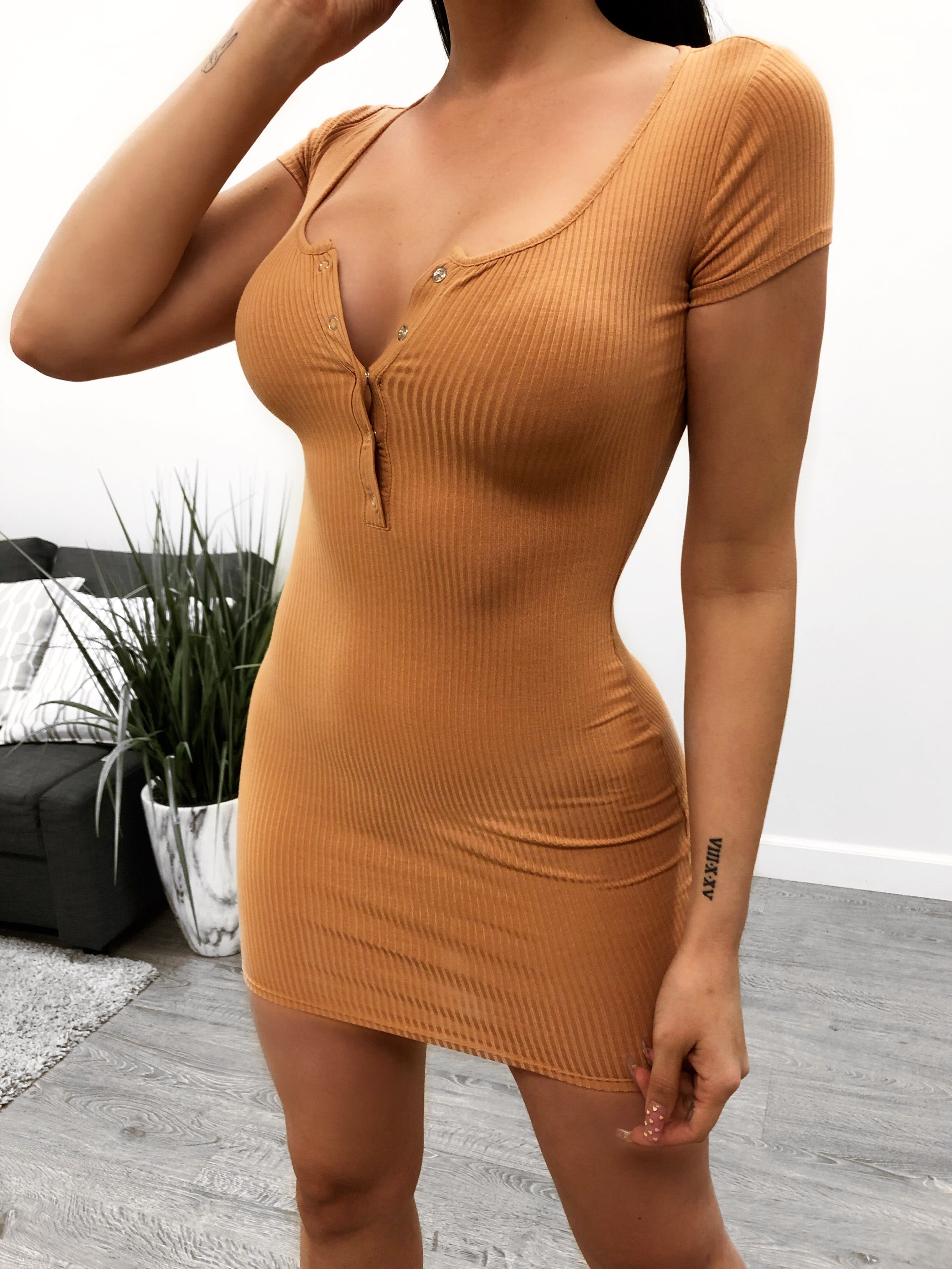 orange rust like short dress. short sleeves. adjustable silver flat buttons in middle cheat area. above mid thigh length. very tight.