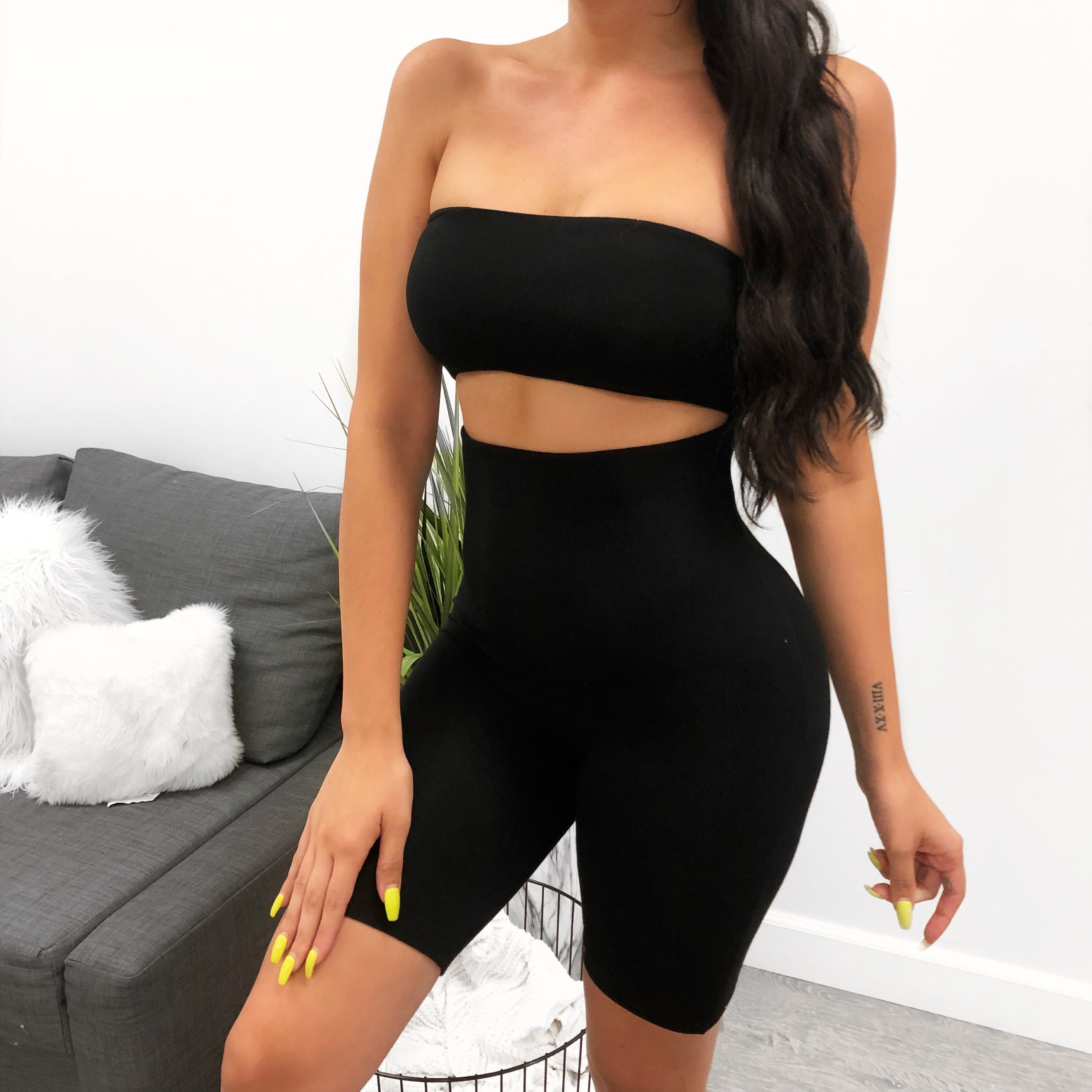 black jumpsuit, the top half is a sleeveless tube top, bottom half is biker shorts, mid thigh length