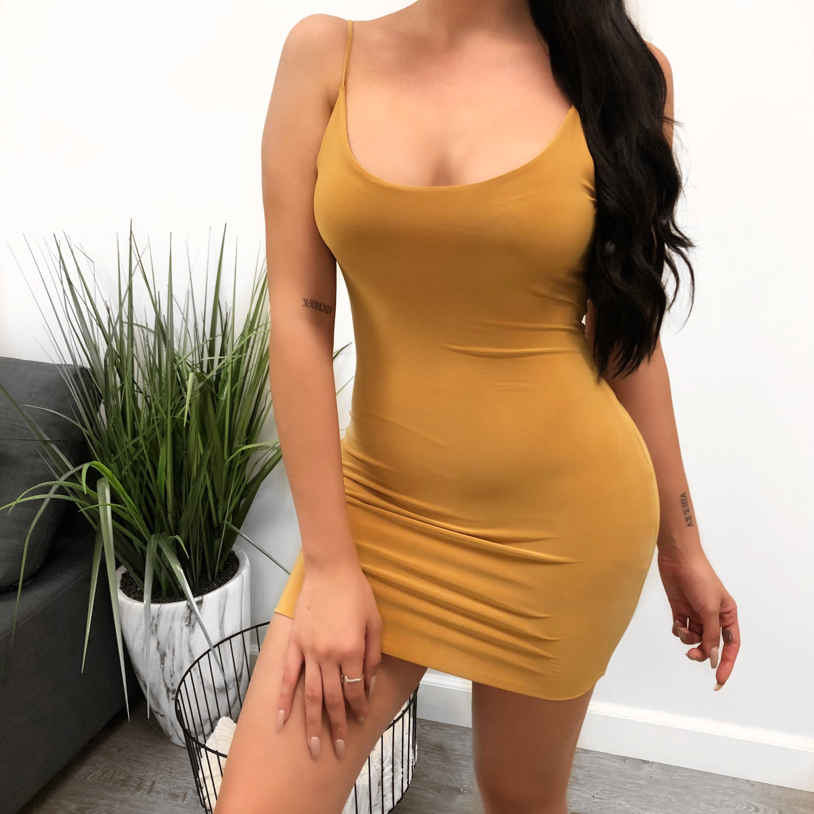 mustard color dress with spaghetti straps. wide u shape with mid cleavage visibility. dress length is mid thigh.  back of dress has a wide u shape as well to mid back.