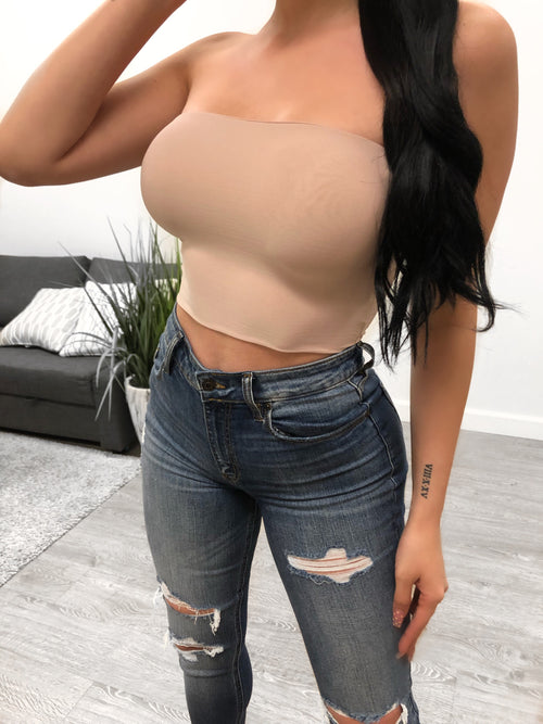nude color tube top. top shows upper breast. top length ends above belly button.