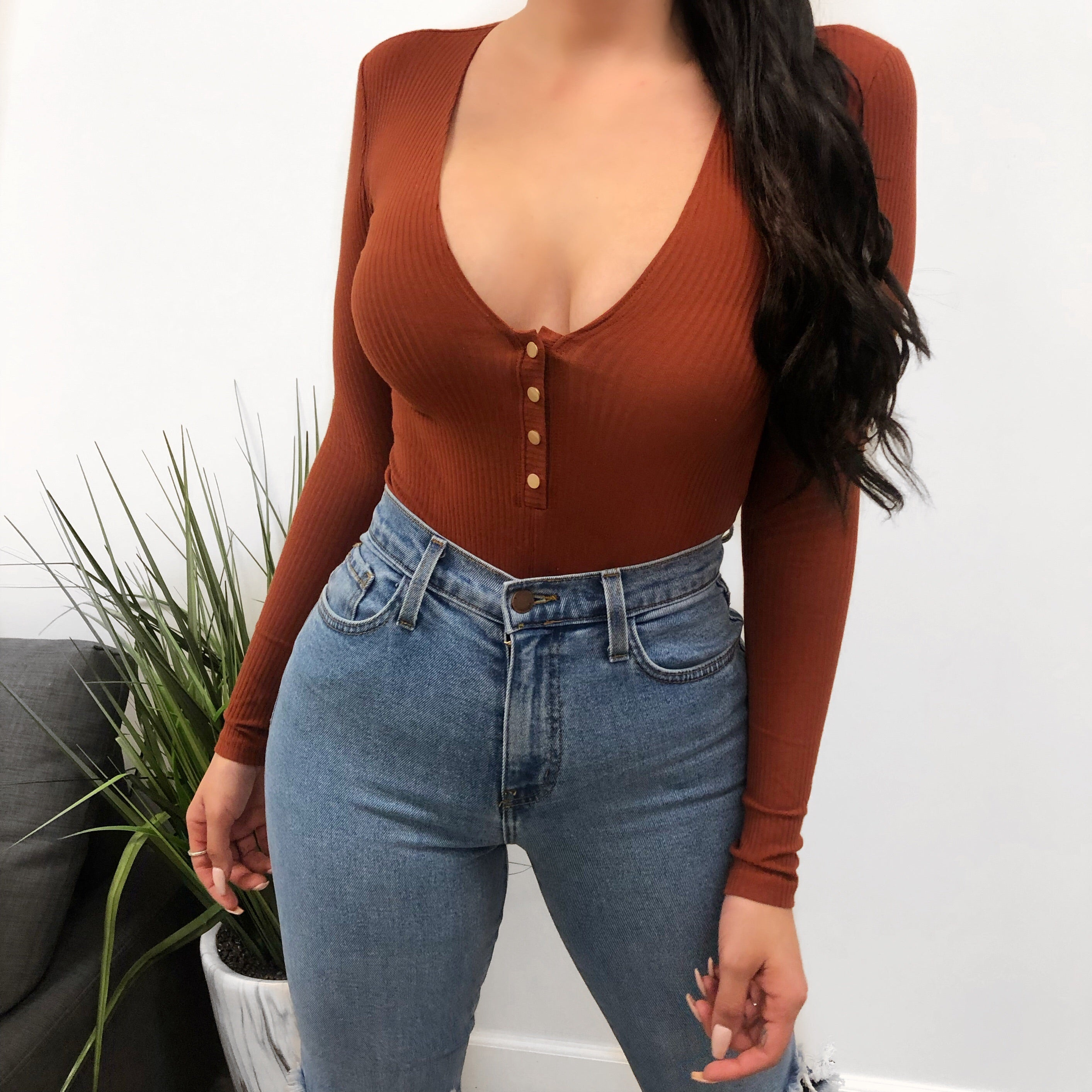 rust long sleeve bodysuit. flat silver buttons in the middle area for style. low cut v neckline. shows cleavage.