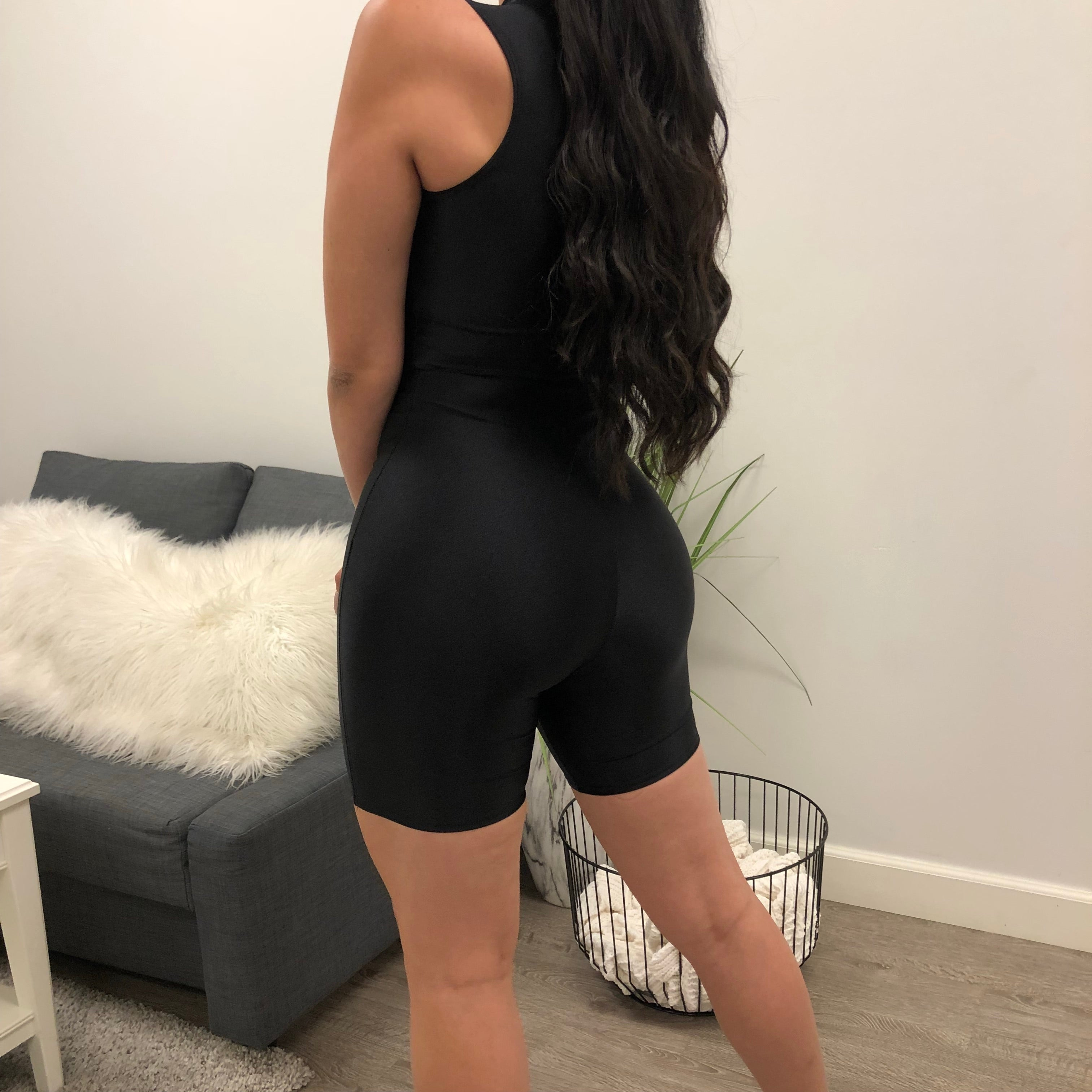 82% Nylon  18% Spandex . Zipper on the middle. Black Jumpsuit is stretchy material. Midi legnth. Very comfortable.