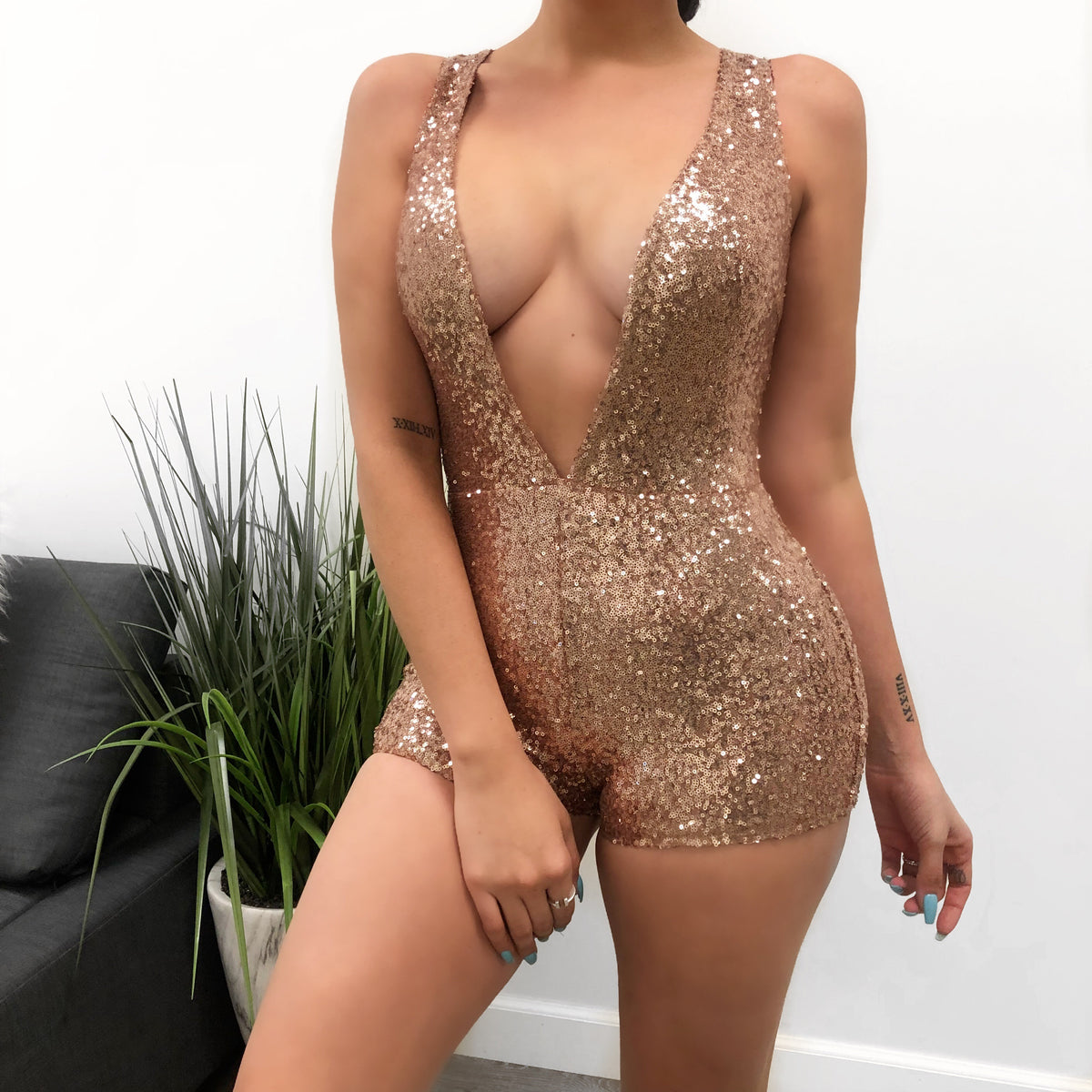 blush sequined romper. tophalf has deep v-cut from neckline to waist. shows cleavage. thick straps for sleeveless.