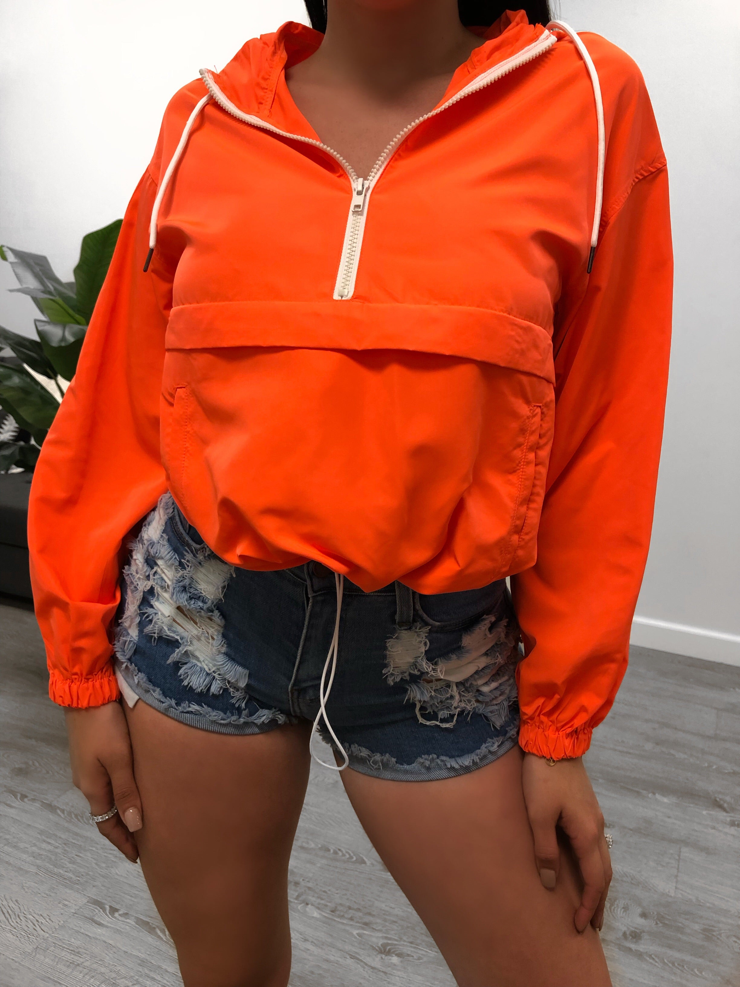 neon orange loose fit jacket, zipper in the front that goes from top of stomach to neck, has zipper pocket in the front, also has hoodie