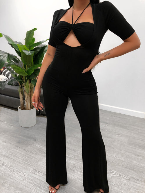 black jump suit. bell bottom length pants with sleeves that end at elbow. fully open chest with a halter top bralette.