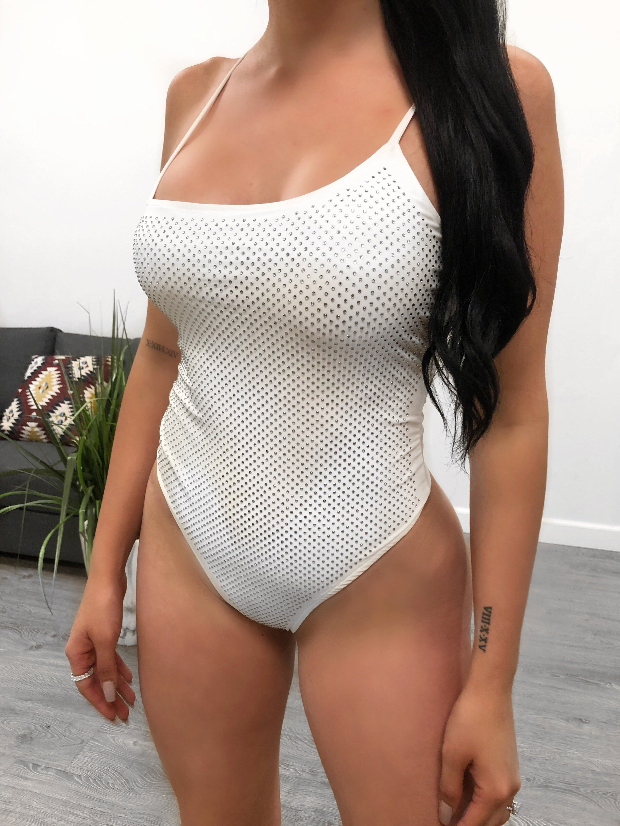 white spaghetti strap one piece bathing suit with low u shape that shows mid cleavage. bathing suit front is cover is circle shape diamond studs mid back is visible. very cheeky bottom