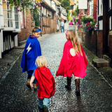 Three children walking down a street, they are dressed as superheroes and the older two are looking back at the younger child