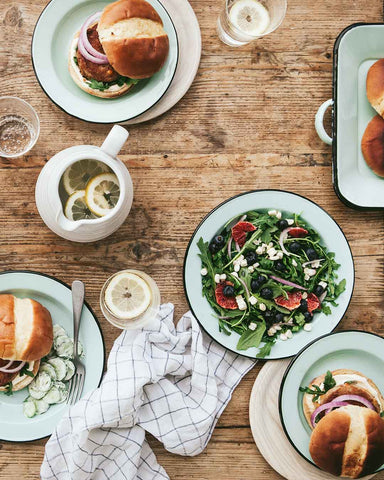 Enamelware dinnerware with burgers and salad on summer table