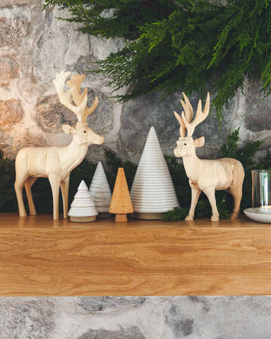 handcarved wood reindeer on holiday mantel