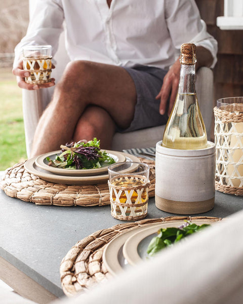 Outdoor summer table with wrapped glasses and handmade dinner plates
