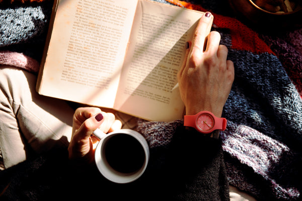 A reader curls up with a warm beverage and a good book.