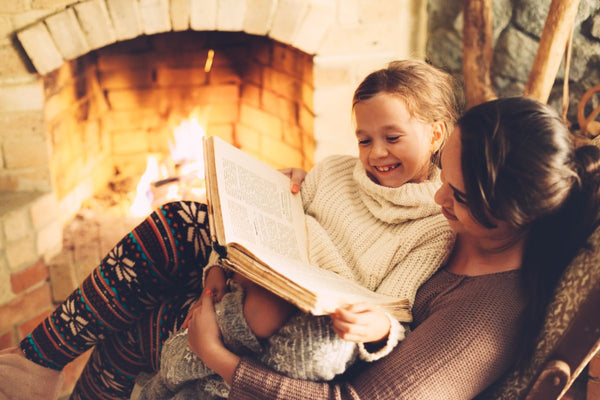 Mom reads to child next to the fireplace.