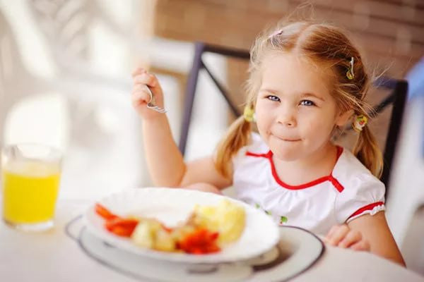 Little girl eating nutritious meal.