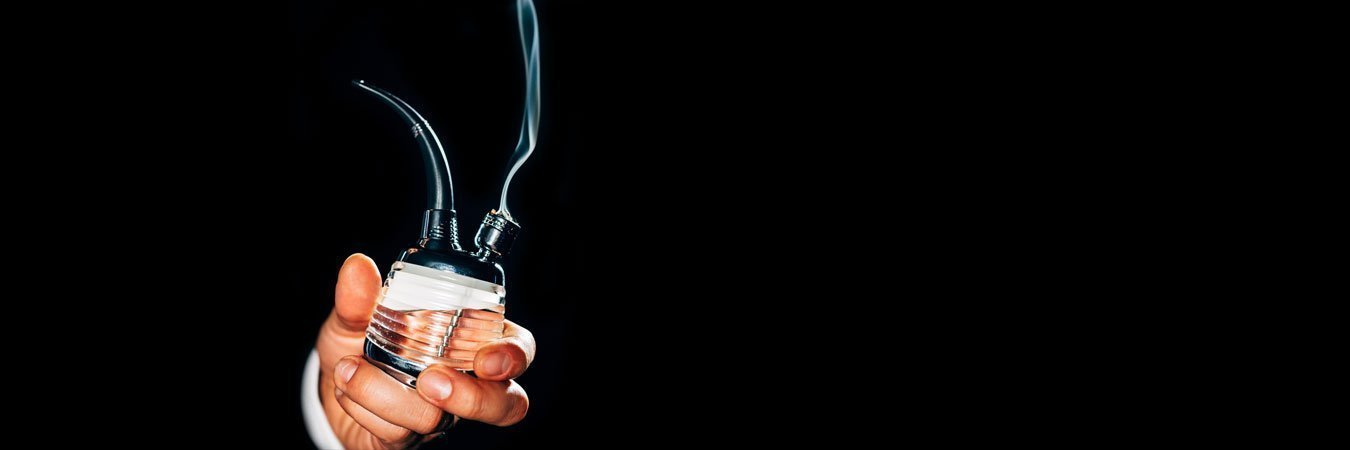 man holding bubbler pipe on black background