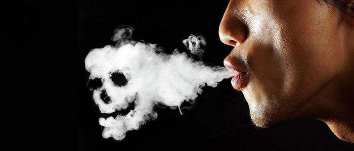 man blowing smoke cloud in the shape of a skull on a black background