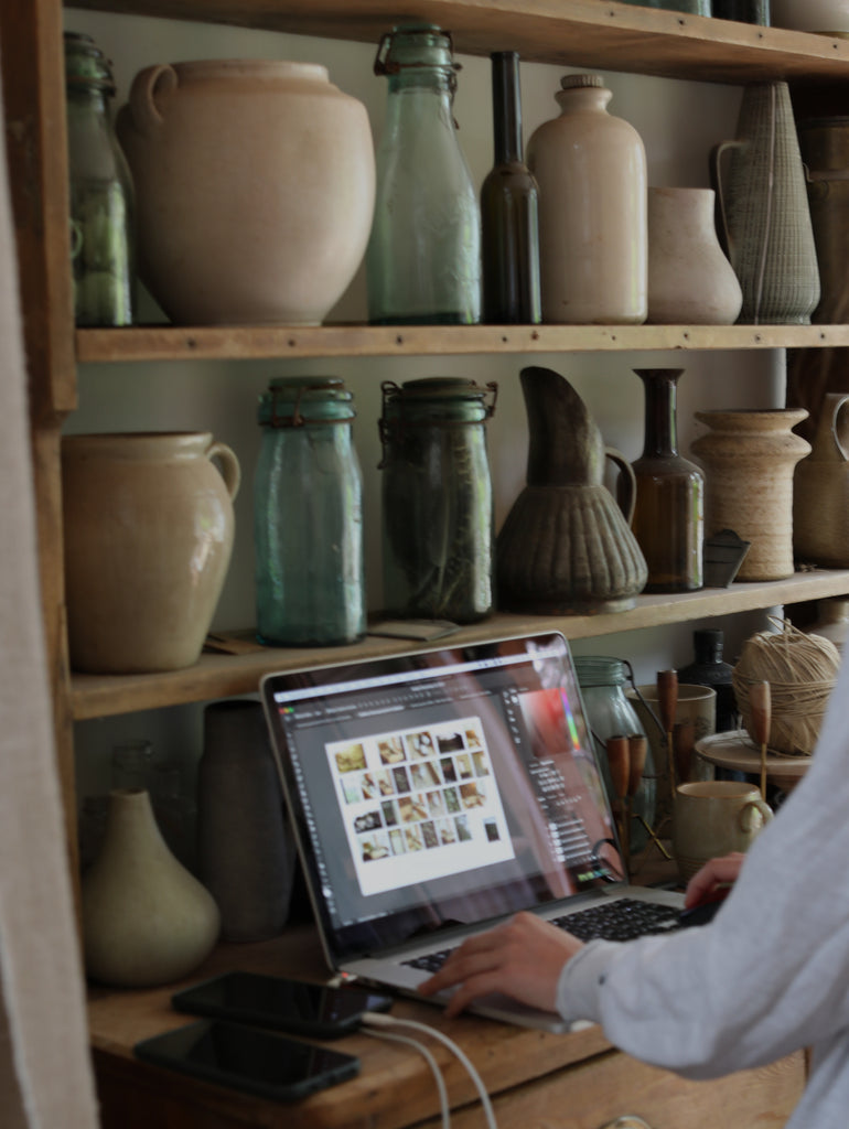 looking at images from shoot on laptop in a room surrounded by antique bottles and pots