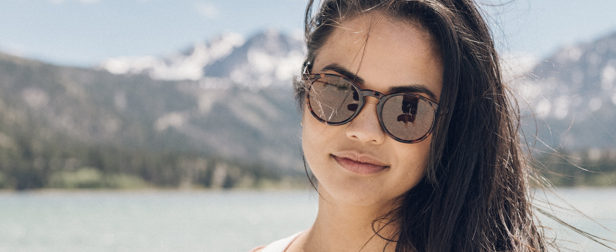 woman wearing tortoise shell sunglasses by the ocean