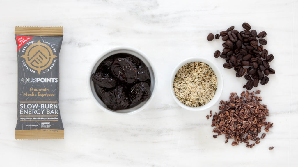 Mountain Mocha Espresso plant-based energy bar, surrounded by prunes and real coffee beans.