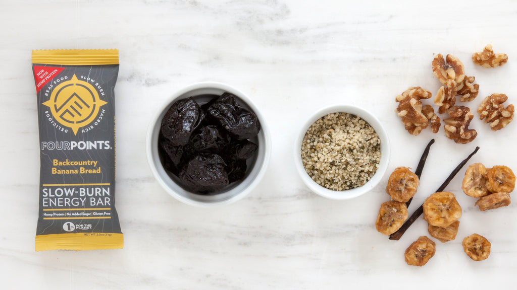 Backcountry Banana Bread plant-based energy bar, surrounded by prunes and real bananas.