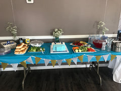 The food table for this baby shower. Notice the cute suspenders on his onesie cake!