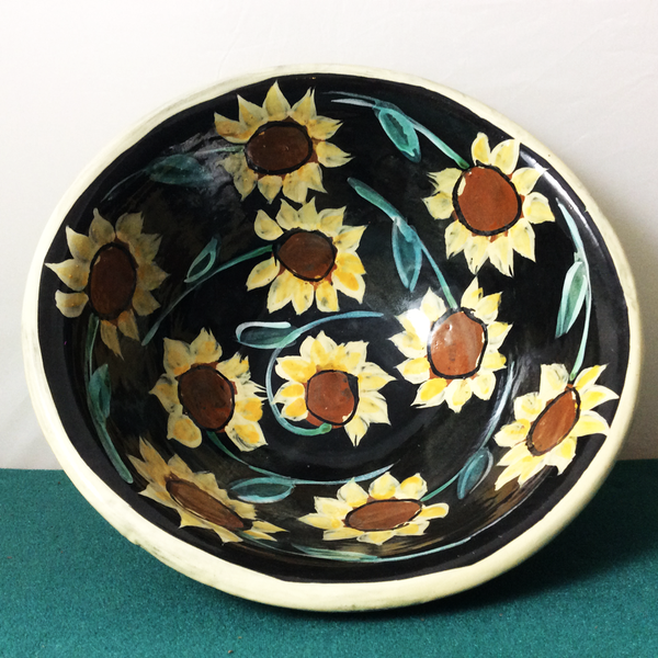 Bowl with sunflowers on black