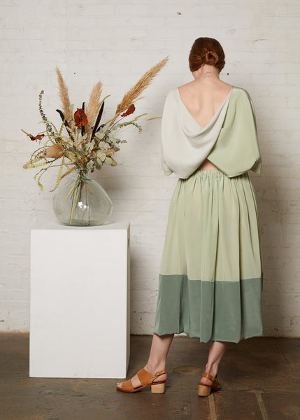 Twist back top in green with skirt viewed from rear
