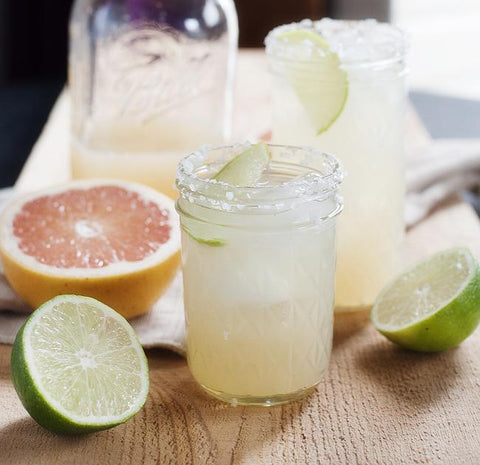 a pink grapefruit margarita in a clear glass with half a pink grapefruit and two halves of lime