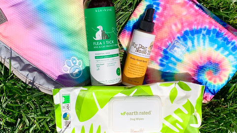 Five products are laying on top of grass. From left to right is the Canada Pooch Cooling Vest which is an ombre rainbow color, followed by a bottle of the Kin and Kind Flea and Tick Spray in a black bottle with a green label, followed by My Dog Nose It Sunscreen in a black bottle with white and yellow, followed finally by the Canada Pooch Cooling Bandana that is a rainbow tie-dye. Underneath all of those products is a small container of the Earth Rated Lavender Wipes; the packaging is mostly white with green leaves on the edges.