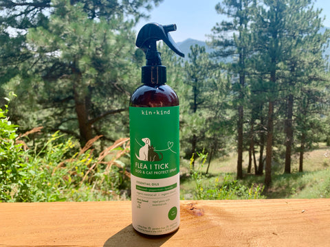 A bottle of the Kin and Kind Flea and Tick Spray sits upon a wooden plank with trees and bushes behind the bottle.