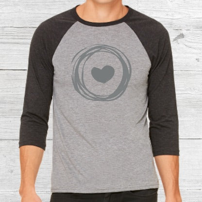 Light gray baseball shirt with dark grey sleeves. Grey Corazon de Vida logo is printed on front.