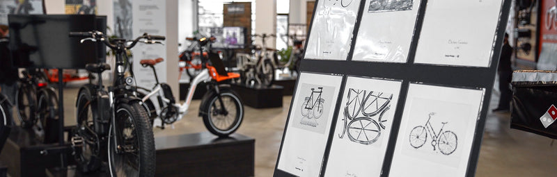 Art provided by 88bikes on display in Rad Power Bikes' showroom next to electric bikes.